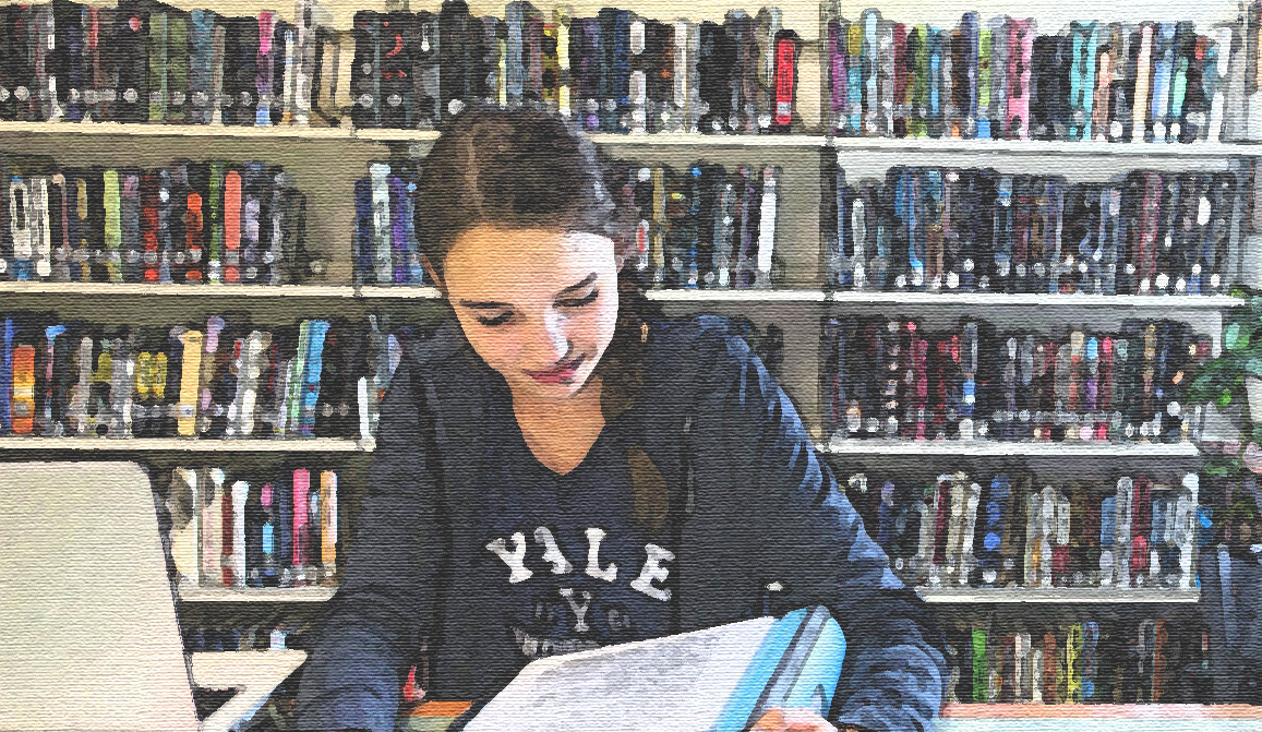 female student reading in the library at DHHS